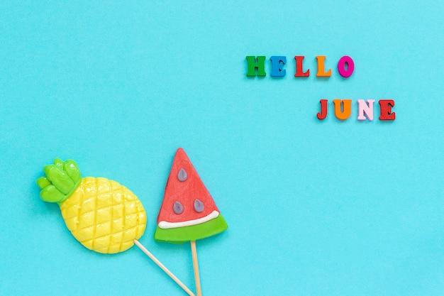 Hallo juni, ananas en watermeloen-lolly's op stok. concept vakantie of vakantie