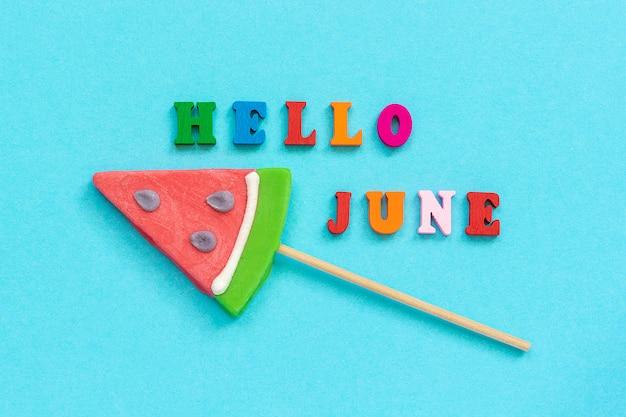 Hallo juni-tekst en watermeloen-lolly's op stok. concept vakantie of vakantie