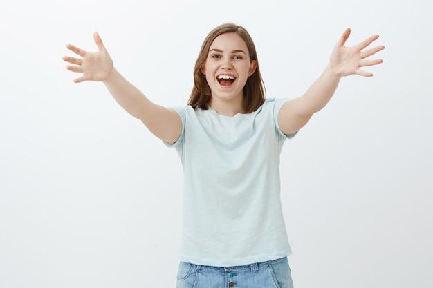 Hallo, lang niet gezien. vriendelijk, vrolijk, aardig meisje met kort bruin haar dat handpalmen trekt in begroetingsgebaar naar hallo zeggen, warm welkom heten en vriend omhelzen over grijze muur glimlachend gelukkig