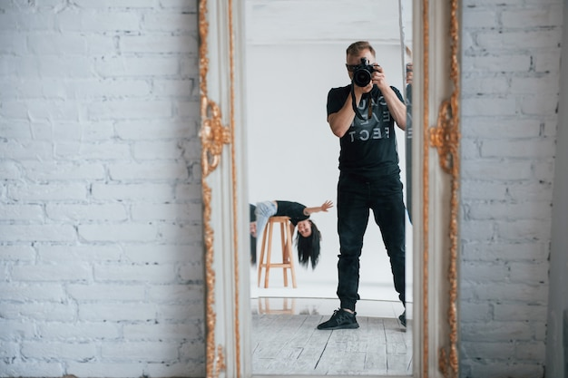 Hallo laten zien. man met camera die een schot in de vintage spiegel neemt. het meisje heeft erachter plezier