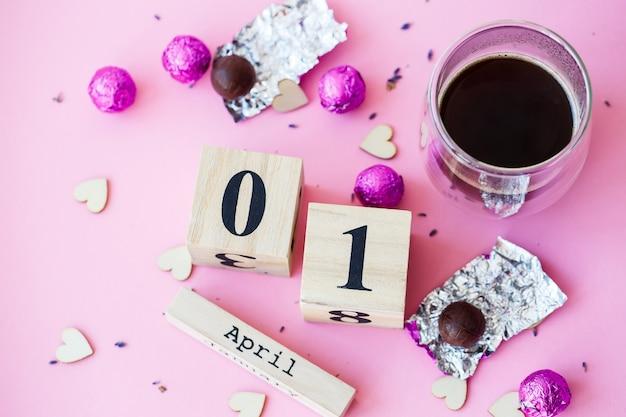 Hallo lente. houten kalender met datum 1 april, op roze achtergrond. wereld lachdag