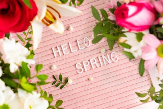 Hallo lente op roze letterbord en frame van bloeiende bloemen. concept lente stemming en geluk.