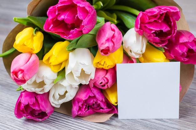 Hallo lente tijd concept. close-up foto van mooi boeket van veelkleurige roze geel witte bloemen in papieren verpakking met briefkaart liggend op grijs houten bureau
