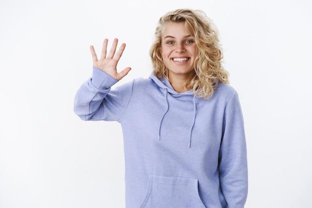 Hallo leuk je te ontmoeten. leuke en vriendelijke uitgaande blondine met kort kapsel en blauwe ogen zwaaiend met opgeheven palm in hallo en begroetend gebaar of gedag glimlachend aangenaam naar camera over witte muur