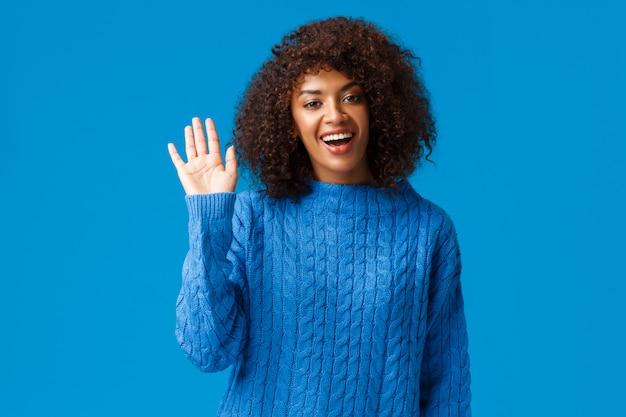 Hallo leuk je te ontmoeten. leuke vriendelijke afro-amerikaanse vrouw zegt hallo en zwaait camera glimlachend als staande in de winter trui over blauwe achtergrond, vriend zien, kom langs voor een praatje