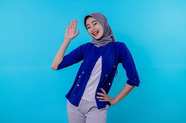 Hallo leuk je te ontmoeten. schattig en vriendelijk extravert blond met het dragen van hijab die met opgeheven hand zwaait in hallo en begroetend gebaar of gedag zegt met glimlachen