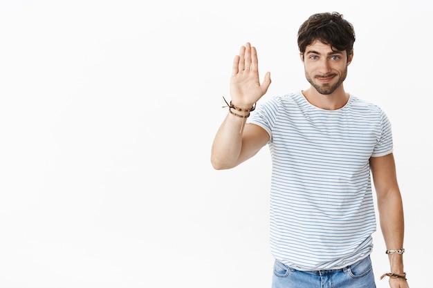 Hallo maat geef een high five. portret van vriendelijke uitgaande knappe jonge mannelijke man met borstelharen en blauwe ogen die de arm opheft om te golven en hallo te zeggen, vriendelijk glimlachend naar voren over de witte muur