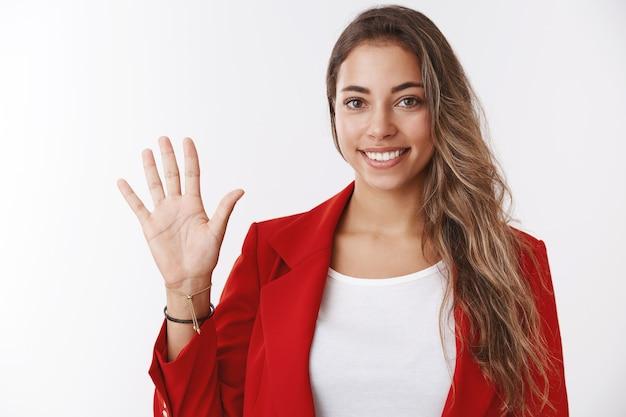 Hallo. meisje zwaait met je en zegt hallo vriendelijk glimlachend, ziet er positief uit met palmbegroeting, verwelkomt nieuwkomers die gezelschap binnenkomen, staat zelfverzekerd aangenaam grijnzende witte muur