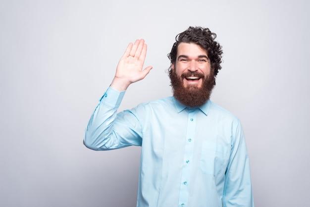 Hallo mensen, lachende bebaarde man in casual groetend gebaar.