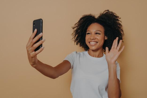 Hallo! mooie vrolijke vrouw met een donkere huid die lacht naar de camera op moderne smartphone, selfie op mobiele telefoon neemt en zich gelukkig voelt, hallo gebarend terwijl ze videogesprek voert, geïsoleerd over studiomuur