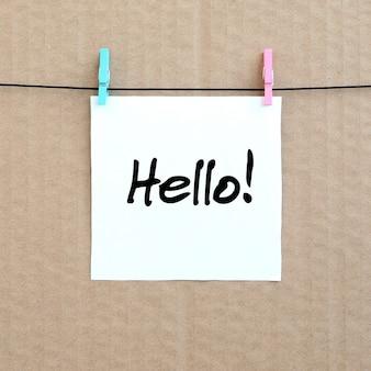 Hallo! opmerking staat op een witte sticker die met een wasknijper hangt