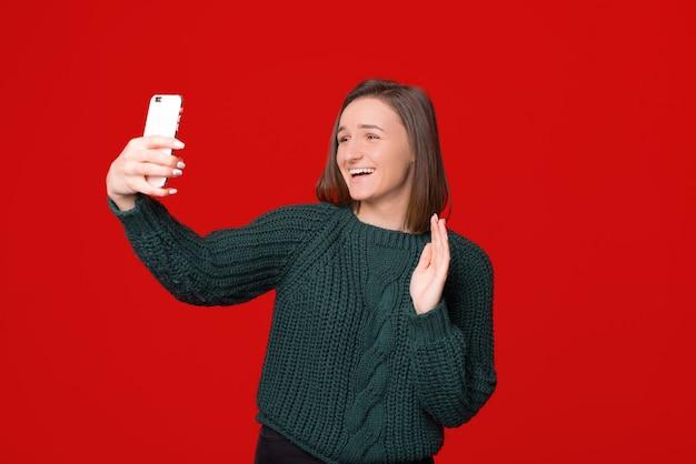 Hallo! portret van vriendelijk meisje hallo gebaar zwaaien en videogesprek voeren op mobiele telefoon, staande over rd geïsoleerde achtergrond