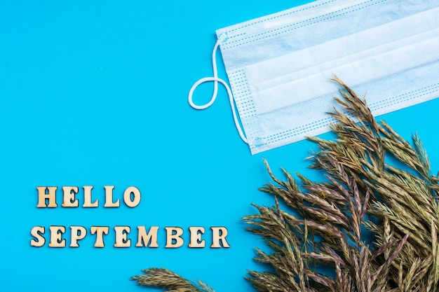 Hallo september-tekst in houten letters en grasoren met beschermend masker