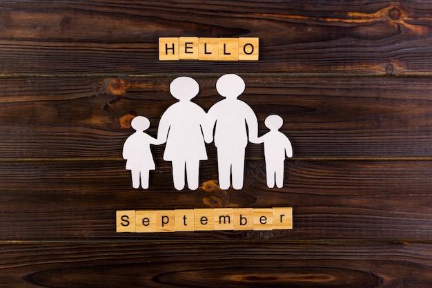 Hallo september woord met papieren silhouet van familie.
