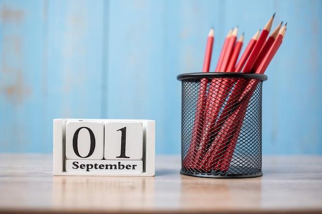 Hallo septemberkalender, welkom terug naar school met notitieboekje en potloden. kopieer ruimte voor tekst