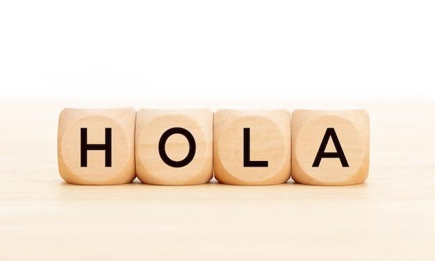 Hallo woord in de spaanse taal in houten blokken op tafel.