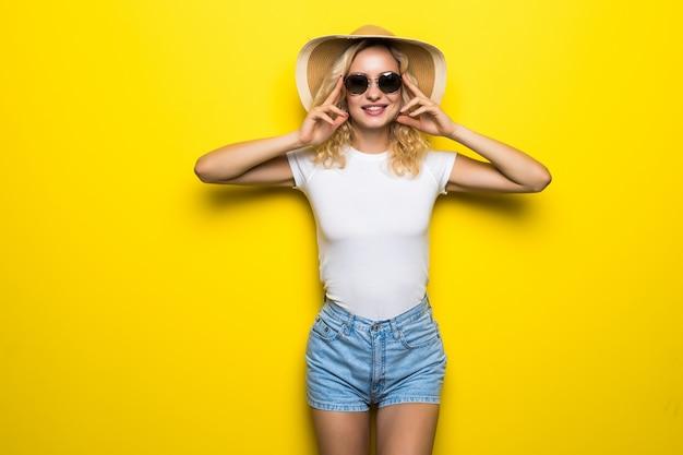 Hallo zomer. de aantrekkelijke jonge vrouw in zonnebril stelt met strohoed die op gele muur wordt geïsoleerd.