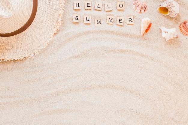 Hallo zomer inscriptie met schelpen en strooien hoed