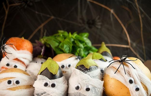 Halloween-achtergrond. griezelige groenten met ogen in medische verbanden op een donkere achtergrond. halloween-eten. baner. kopie van de ruimte.