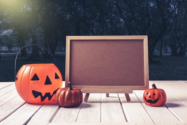 Halloween achtergrond. griezelige pompoen, bord op houten vloer en donker bos. hallowee