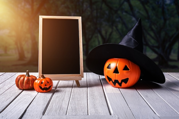 Halloween achtergrond. griezelige pompoen, bord op houten vloer en donker bos.