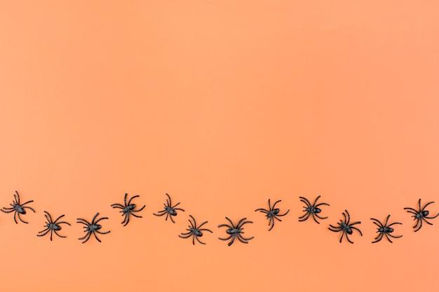 Halloween-achtergrond met de spinnen op oranje achtergrond.