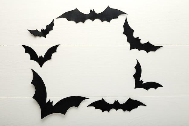 Halloween achtergrond met papier vleermuizen op witte houten achtergrond. kader. halloween decoraties voor de feestdagen. plat lag, bovenaanzicht, kopieer ruimte. feestuitnodiging mockup, feest.