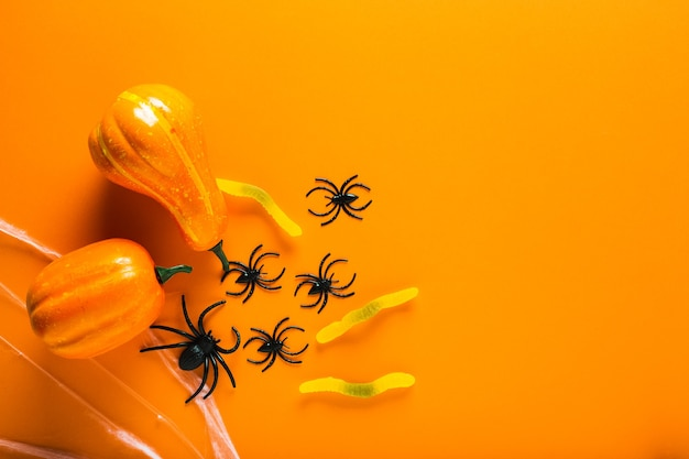 Halloween-achtergrond met pompoenen, snoepworm, spinnenweb en spinnen als symbolen van halloween op de oranje achtergrond. gelukkig halloween-concept. bovenaanzicht met kopie ruimte.