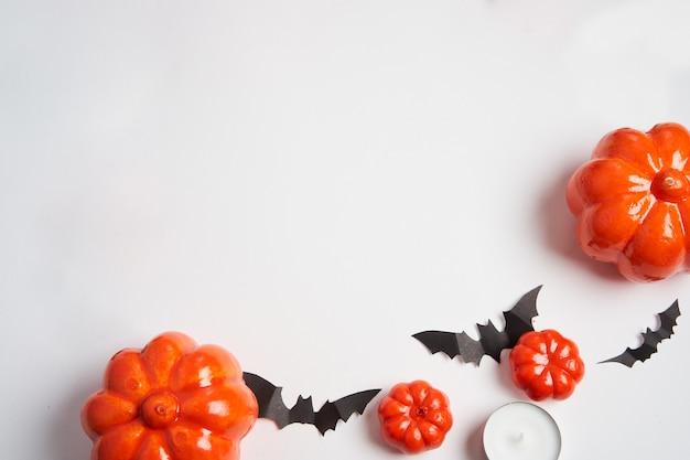Halloween-achtergrond, oranje decoratief plastic pompoen zwart document vleermuis wit karton