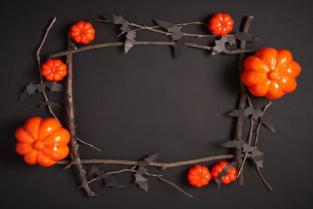 Halloween-achtergrond, oranje decoratief plastic pompoen zwart document vleermuis zwart karton