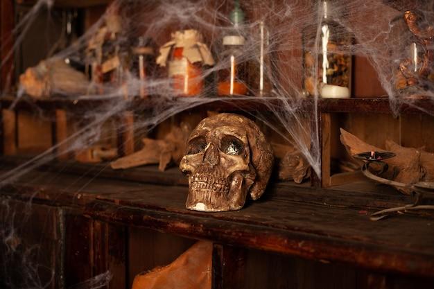 Halloween-achtergrond planken met alchemiegereedschap schedelspinnenwebfles met gifkaarsen witcher-werkruimte scarry-kamer