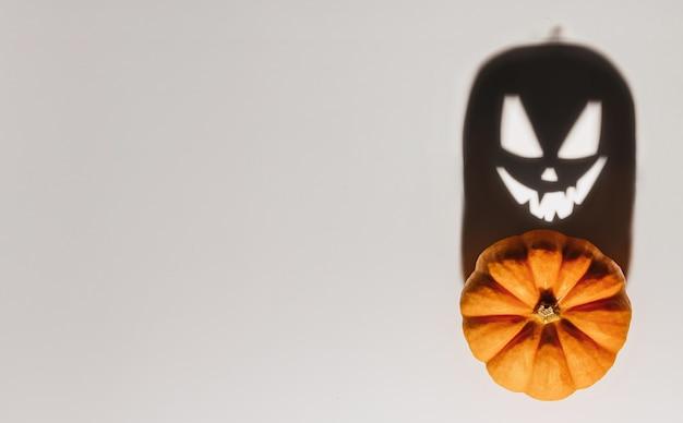 Halloween-achtergrondconcept. jack o pompoen boos gezicht schaduw. spooky lachende schaduw van een oranje pompoenlantaarn bovenaanzicht close-up, halloween-feestontwerp