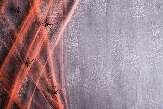 Halloween-ambachten, oranje spinneweb met spin op grijze achtergrond