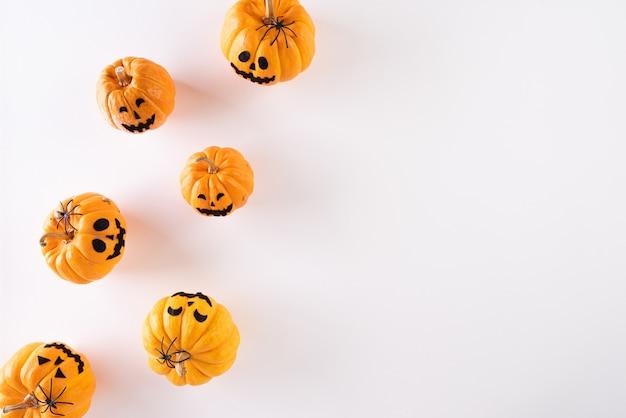 Halloween-ambachten, oranje spookpompoen op witte achtergrond met exemplaarruimte