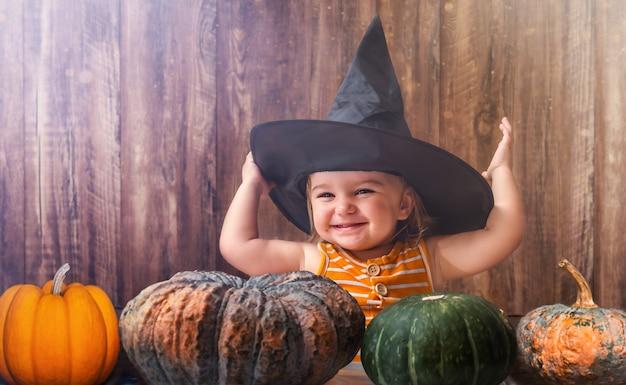 Halloween-baby met pompoenen in heksenhoed op houten achtergrond