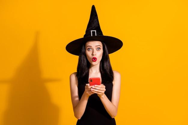 Halloween bijna afgelast. foto van schattige mooie jonge goochelaar dame houdt telefoon verbaasd thema-evenement uitgesteld draag zwarte tovenaar hoofddeksels jurk geïsoleerd felgele kleur achtergrond