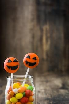 Halloween-cake knalt en gekleurd suikergoed op rustieke houten muur