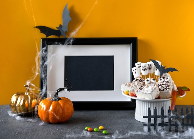 Halloween candy bar: grappige monsters gemaakt van koekjes met chocolade en gummy wormen, spoken marshmelow close-up op tafel