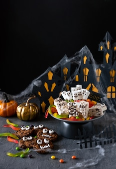 Halloween candy bar grappige monsters gemaakt van koekjes met chocolade en spoken marshmallow close-up op tafel. halloween feestdecoratie. trick or treat-concept.