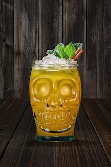 Halloween-cocktail in drinkbekerschedel op houten plank.