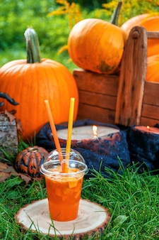 Halloween-cocktail met pompoendecoratie op achtergrond. punch voor een feestje. jack-o-lantern.