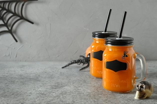 Halloween-cocktail met pompoensap, kruiden, wortel versiert spinnen en schedel voor feestelijk feest op grijs