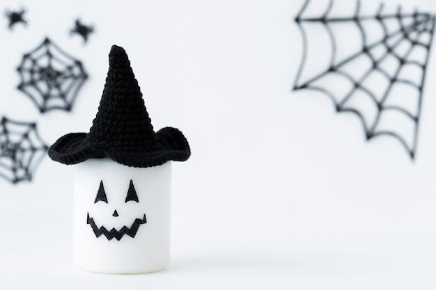 Halloween-concept eng gezicht van kaars in zwarte hoed op een grijze vakantieachtergrond