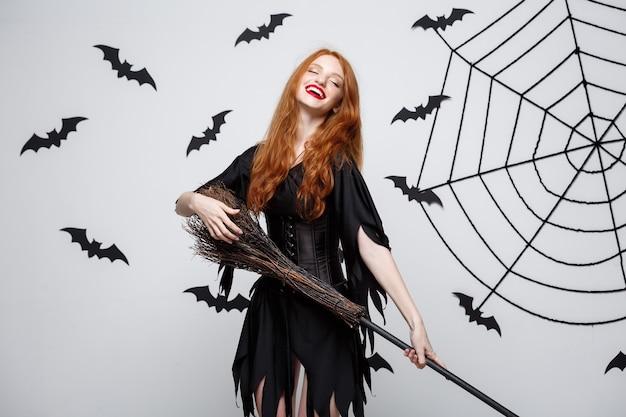 Halloween concept gelukkige elegante heks geniet van spelen met bezemsteel halloween-feest over grijze muur