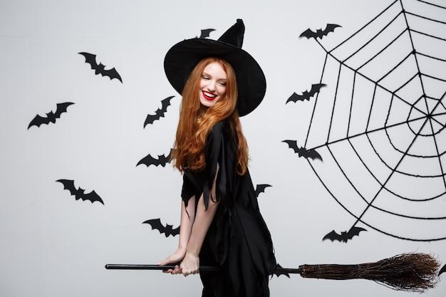 Halloween concept gelukkige elegante heks geniet van spelen met bezemsteel