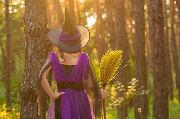 Halloween-concept. jong meisje in een halloween-kostuum in het bos met een bezem.