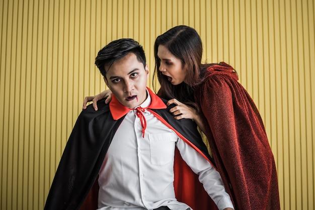 Halloween-concept jonge aziatische vrouw in kostuumheks en aziatische man in kostuumdracula op gele achtergrond. portret tiener paar verkleed als heksen en dracula voor het vieren van halloween festival.
