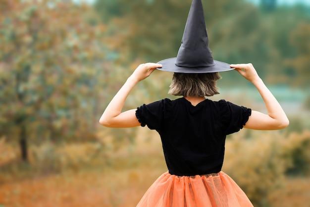 Halloween-concept jonge heks in de zwarte hoed die achteruit gaat