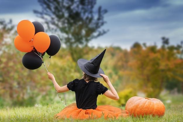 Halloween concept jonge heks in het zwart met ballonnen en grote pompoen