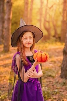 Halloween-concept. meisje verkleed als heks met pompoen in haar handen op bosachtergrond.